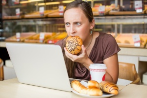 Pretty young woman working at the computer and eat bread. Unhealthy Lifestyle